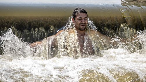 A man cools off in a weir on the Berounka river close to village of Dobrichovice, Czech Republic. (AAP)