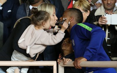 Patrice Evra kisses Sandra while his children Lenny Evra and Maona Evra look on after the UEFA Champions League Quarter Final.