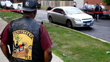 A bystander watches as Chicago Police officers and detectives investigate a shooting where multiple people were shot on Sunday, August 5, 2018 in Chicago, Illinois.