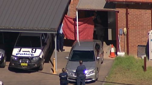 Police hold up a sheet as Vincent Stanford is transferred to Griffith Local Court. (9NEWS Choppercam)