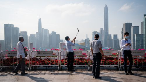People take photographs against a backdrop of the Shenzhen skyline at Lianhuashan Park in Shenzhen, China