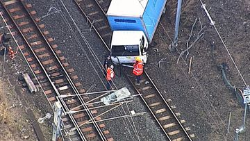 Truck crashes on train tracks in Brisbane causing major delays.