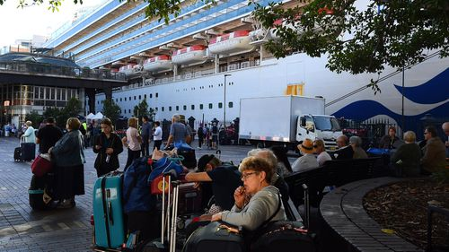Passengers sit with their luggage after disembarking from the Ruby Princess cruise ship at the Overseas Passenger Terminal in Circular Quay, Sydney