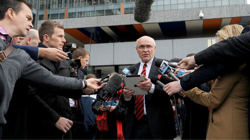 Essendon Chairman Paul Little reads out a statement to waiting media outside the Federal Court in Melbourne where the club and the ASADA were convening. (AAP Image/Joe Castro)