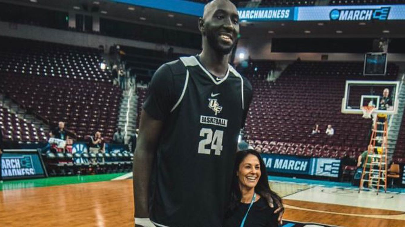 Basketball giant Tacko Fall standing next to reporter Tracy Wolfson is amazing