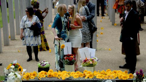 People comfort each other following a service at the July 7 memorial in Hyde Park, London. (AAP)