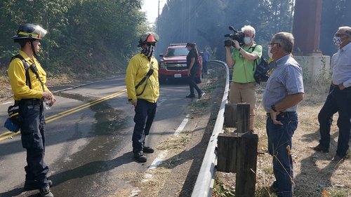 Washington Gov. Jay Inslee, second from right, joins Pierce County Executive Bruce Dammeier, third from right, and East Pierce Fire and Rescue Chief Bud Backer, right, in talking with firefighters, Wednesday, Sept. 9, 2020, during a tour to survey wildfire damage in Bonney Lake, Wash., south of Seattle. (AP Photo/Ted S. Warren, Pool)