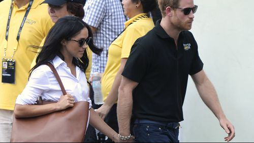 Harry and Megan holding hands.at the Invictus Games.