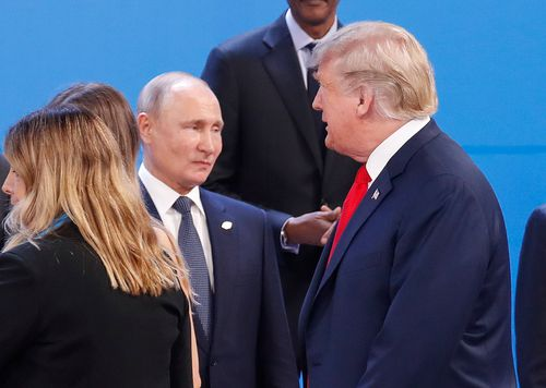 Trump walks past Russia's President Vladimir Putin as they gather for the group photo at the start of the G20 summit in Buenos Aires, Argentina.