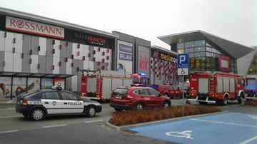 Police and firefighters' cars and trucks stand in front of the VIVO! shopping mall where a 27-year-old man attacked people with a knife, killing one person and injuring several others in Stalowa Wola, southeastern Poland. (AP)