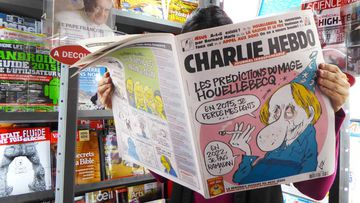 A woman reads the latest issue of French satirical newspaper 'Charlie Hebdo' in a bookshop in Paris, France. (AAP)