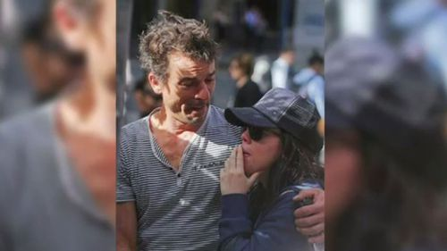 Harriette Denny, comforted by her partner, at the memorial in Martin Place. (9NEWS)