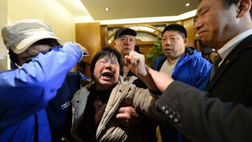 A relative of passengers on Malaysia Airlines flight MH370 waves her fist as she cries after hearing the news that the plane plunged into Indian Ocean. (Getty)