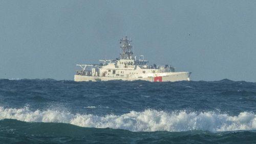 A U.S. Coast Guard cutter patrols the area of debris from a 737 cargo plane that crashed off Oahu.