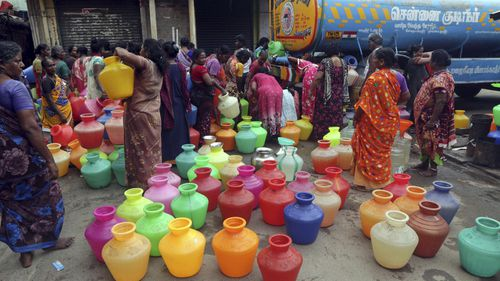 Indians wait to fill vessels filled with drinking water from a water tanker in Chennai.