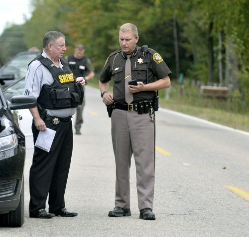 """In this Sept. 27, 2017 photo, Isabella County Sheriff Michael Main, right, coordinates efforts in a police manhunt to locate a suspect in Michigan. Main is apologizing for accidentally leaving his gun in a mid-Michigan school gym locker room. Main said in a statement Tuesday, March 13, 2018, that he takes full responsibility and is """"devastated"""" by his negligence. Main said a student found the gun and immediately contacted an adult. (Lisa Yanick Litwiller /The Morning Sun via AP)"""