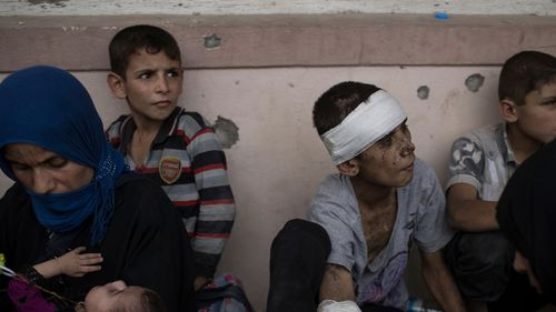 Iraqi civilians sit inside a house as they wait to be taken out of the Old City during fighting. (AAP)