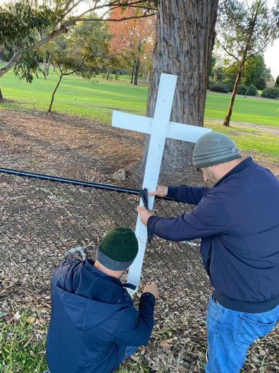 Mr Abdallah and another man rebuilding the memorial for the four children lost in the Oatlands crash.