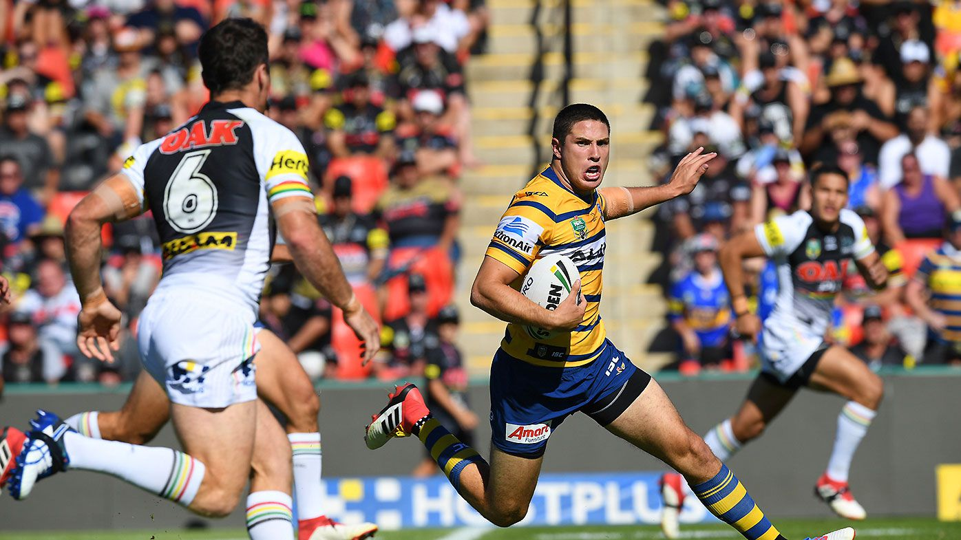 Mitchell Moses (centre) of the Eels runs with the ball against the Panthers