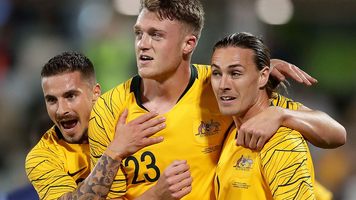 Harry Souttar of the Socceroos celebrates scoring a goal with teammates