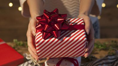 Woman holding wrapped Christmas present 2