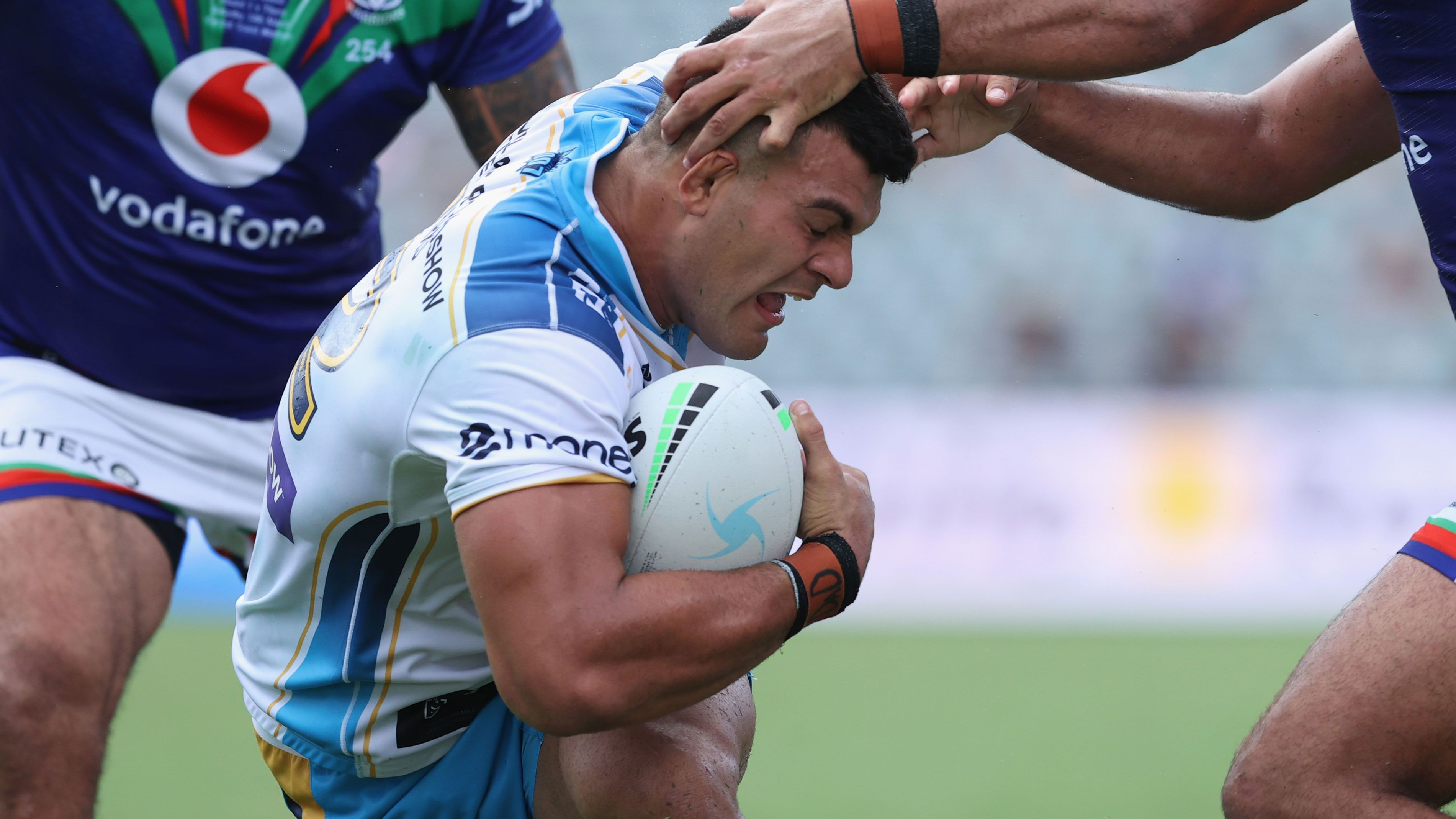 David Fifita is brought down by two Warriors tacklers.
