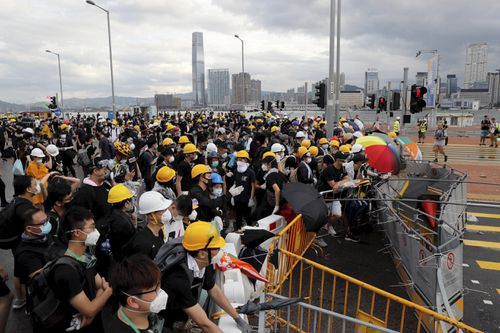 Protesters in Hong Kong pushed barriers and dumpsters into the streets early this morning in an apparent bid to block access to a symbolically important ceremony marking the anniversary of the return of the former British colony to China.
