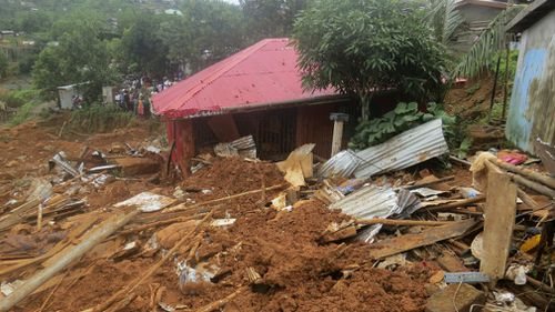 Security forces search for bodies from the scene of heavy flooding and mudslides in Regent. (AAP)