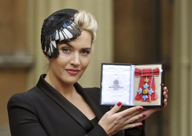British actress Kate Winslet displays her CBE, for services to drama, which was awarded to her by Queen Elizabeth II, during an Investiture ceremony at Buckingham Palace in central London, Wednesday Nov. 21, 2012. (AP Photo/ John Stillwell/Pool)