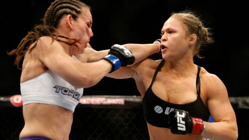 Rousey throws a punch at opponent Alexis Davis. (Getty)