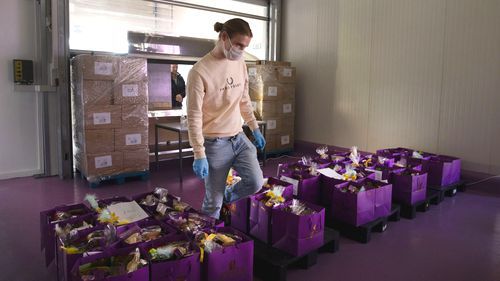 A worker picks orders among bags of chocolate to deliver to a client waiting at a makeshift window at the Chocolate Line warehouse of Dominique Persoone in Bruges, Belgium, Friday, April 10, 2020.