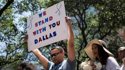 "A man holds a sign proclaiming ""We stand with you Dallas""."