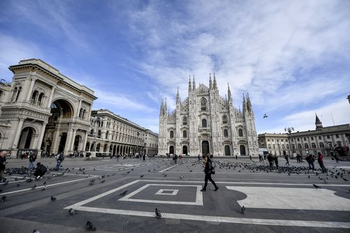 A small number of people walk through the Piazza Duomo in Milan pn February 26. Picture: Claudio Furlan