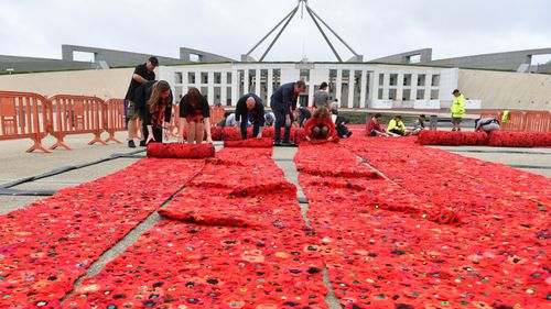 European Union ambassadors help with the installation of 270,000 poppies outside Parliament House in Canberra.