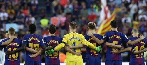 Barcelona players stand for a minute of silence for the victims of the van attacks before a La Liga soccer match between Barcelona and Betis at the Camp Nou stadium in Barcelona. (AP)