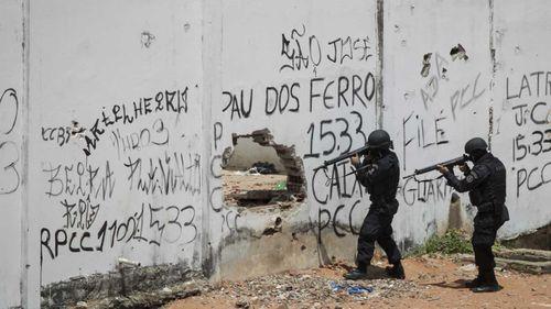 Police enter a jail during a prisoner revolt in Natal, Brazil.