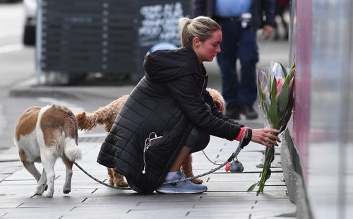 A woman lays flowers after the tourist was killed on Chapel Street.