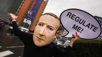 A campaigner from the global citizens movement Avaaz wearing a mask of Facebook CEO Mark Zuckerberg.