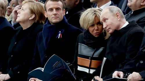 Russian President Vladimir Putin and French First Lady Brigitte Macron talk as they sit alongside French President Emmanuel Macron and German Chancellor Angela Merkel.