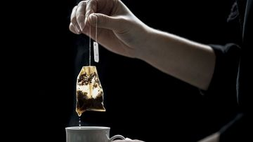 Stock image of a woman holding a tea bag above a cup of tea.