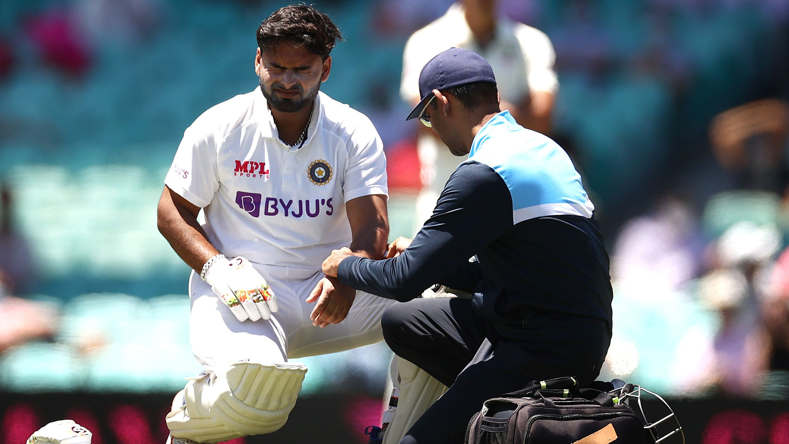 Rishabh Pant of India reacts after being struck by a delivery from Pat Cummins of Australia.