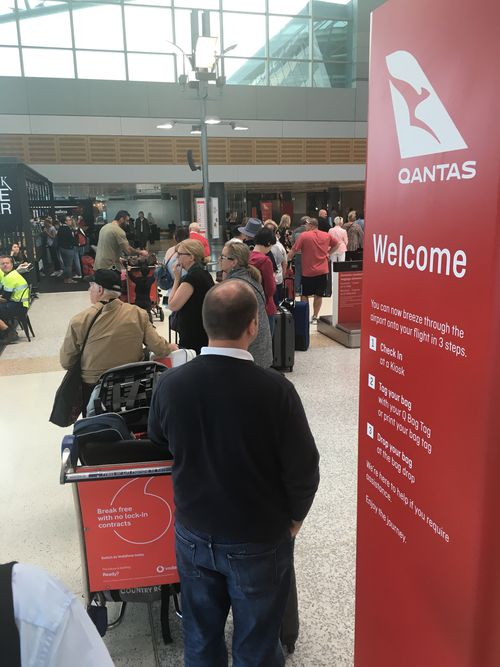 Customers wait for check-in terminals to come back to life after a power outage. Image: Max Roberts
