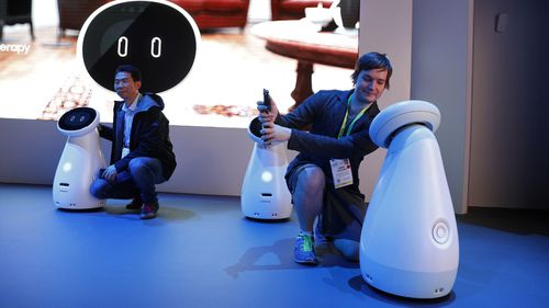 Jason Stettner, right, takes a picture with a Bot Care robot in the Samsung booth at CES.