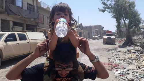 A little girl takes a drink of water in Mosul. (Owen Holdaway)