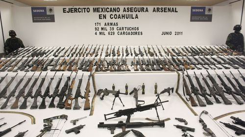 Soldiers stand guard during a media presentation of a weapons cache that includes 154 rifles and shotguns and over 92,000 rounds of ammunition, in Mexico City, in 2011. Authorites believe the weapons belonged to the Zetas drug cartel.