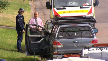 Police inspect a vehicle outside a premises on Ridge Road in Engadine.