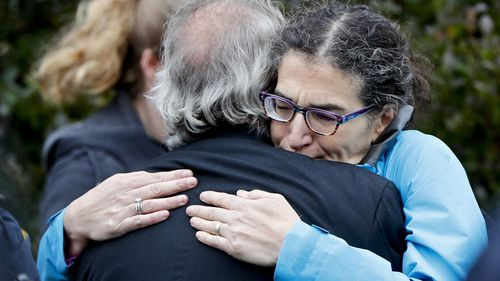 People embrace along the street in the Squirrel Hill neighborhood of Pittsburgh where a shooter opened fire