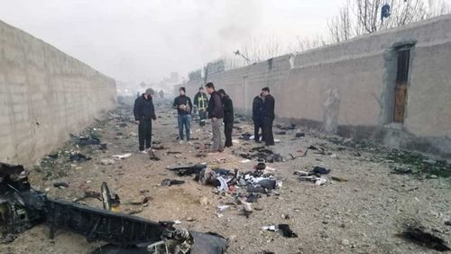 Iranian authorities look through the debris of the plane crash.