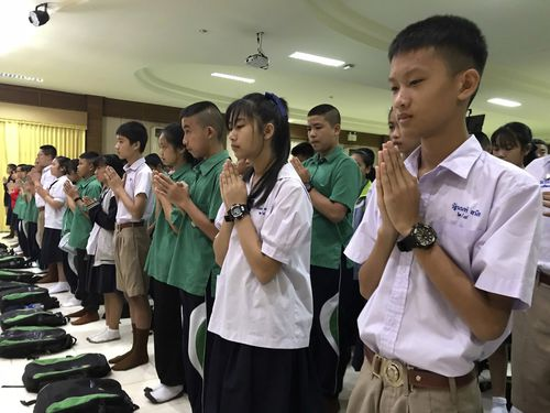 Students pray at Maesaiprasitsart school where six out of the rescued 12 boys study as they marked the successful rescue of the group. Picture: AP