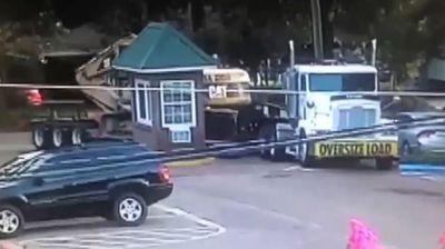 A US university undergoing redevelopment was forced to add another building to its construction plans when a truck's oversized trailer turned a tiny guardhouse into match sticks.
